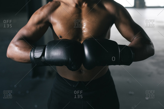 African American man wearing and punching his boxing gloves in an empty urban building. urban fitness healthy lifestyle.