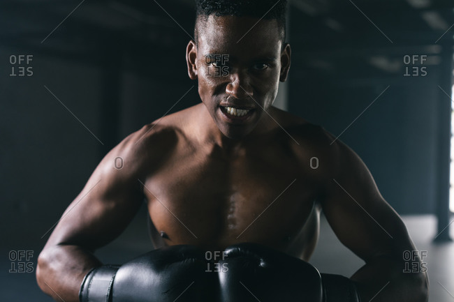 Portrait of African American man wearing and punching boxing gloves in an empty urban building. looking at the camera. urban fitness healthy lifestyle.