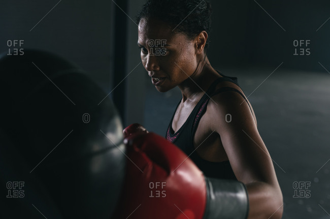 African American woman wearing boxing gloves punching boxing bag in an empty urban building. urban fitness healthy lifestyle.