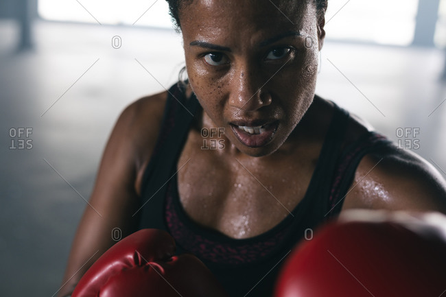 Portrait of African American woman wearing boxing gloves punching boxing bag in empty urban building. urban fitness healthy lifestyle.