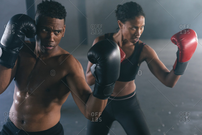 African American man and woman wearing boxing gloves throwing punches in air in empty building. urban fitness healthy lifestyle.