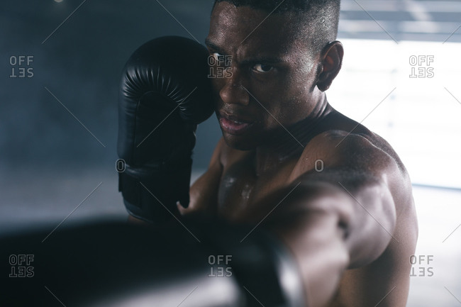 African American man wearing boxing gloves throwing punches in air in empty building. urban fitness healthy lifestyle.