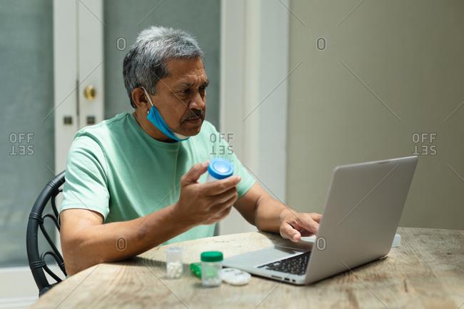 Senior African American man wearing mask holding medicine using laptop. retirement lifestyle in self isolation during coronavirus covid 19 pandemic.