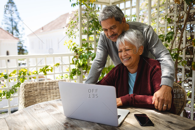 Senior African American couple sitting on terrace using laptop. retirement lifestyle in self isolation during coronavirus covid 19 pandemic.