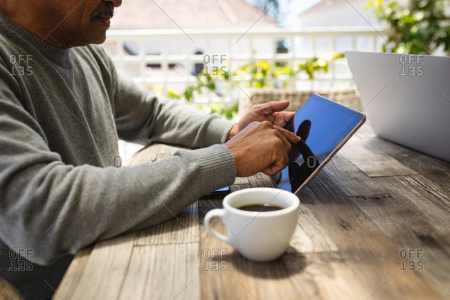 Senior African American man sitting on terrace using digital tablet drinking coffee. retirement lifestyle in self isolation during coronavirus covid 19 pandemic.