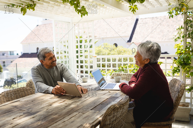 Senior African American couple sitting on terrace using laptop and digital tablet. retirement lifestyle in self isolation during coronavirus covid 19 pandemic.