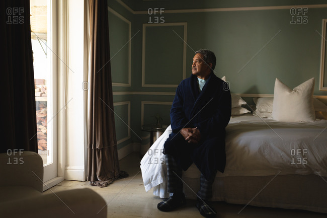 Senior African American man sitting on a bed in a sleeping room. retirement lifestyle in self isolation during coronavirus covid 19 pandemic.