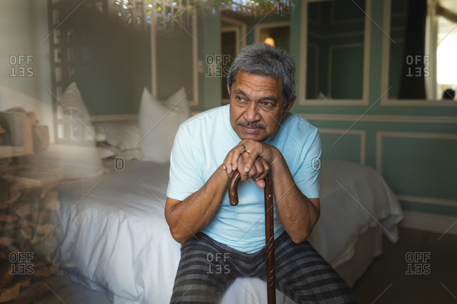 Senior African American man sitting on a bed resting on cane in a sleeping room. retirement lifestyle in self isolation during coronavirus covid 19 pandemic.