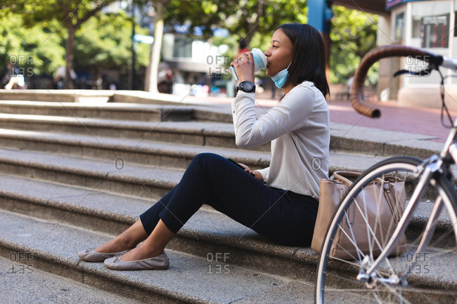African American woman with lowered face mask drinking coffee while sitting on the stairs outdoors. lifestyle living concept during coronavirus covid 19 pandemic.