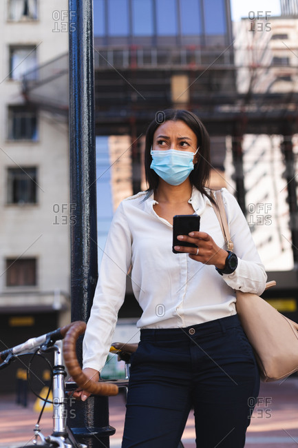 African American woman wearing face mask holding smartphone and standing with bicycle on the street. lifestyle living concept during coronavirus covid 19 pandemic.