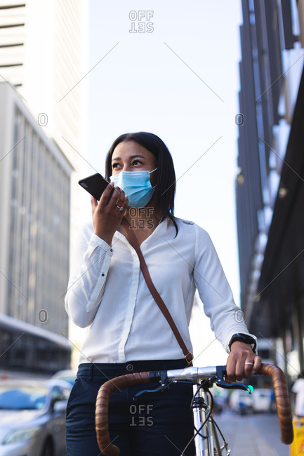 African American woman wearing face mask with bicycle talking on smartphone on the street. lifestyle living concept during coronavirus covid 19 pandemic.
