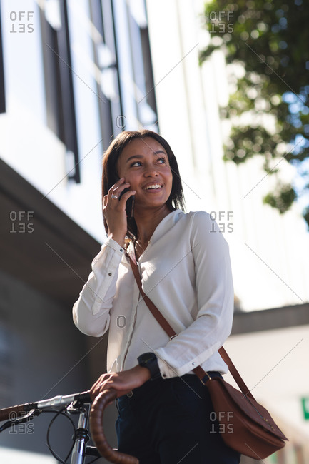 African American woman with bicycle talking on smartphone on the street. lifestyle living concept during coronavirus covid 19 pandemic.