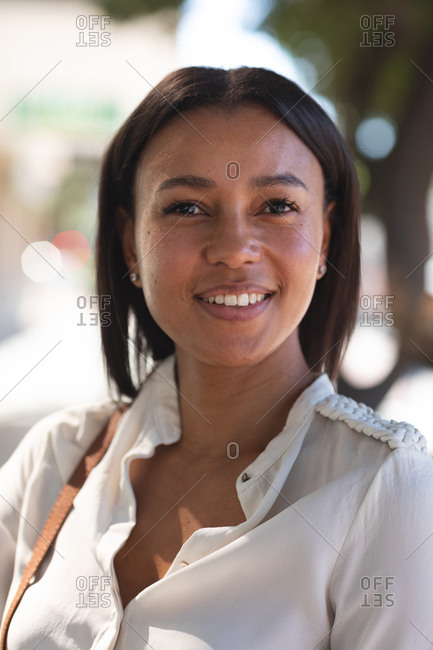 Portrait of African American woman smiling on the street. lifestyle living concept during coronavirus covid 19 pandemic.
