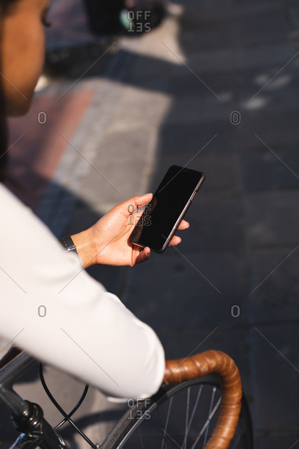African American woman using smartphone while leaning on the bicycle on the street. lifestyle living concept during coronavirus covid 19 pandemic.