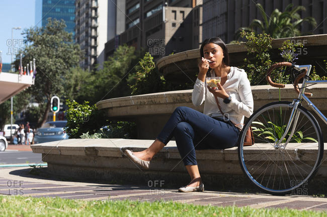 African American woman having a snack while sitting at corporate park. lifestyle living concept during coronavirus covid 19 pandemic.