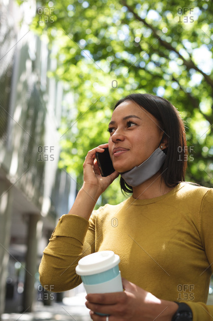 African American woman with lowered facemask talking on smartphone on the street. lifestyle living concept during coronavirus covid 19 pandemic.