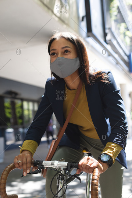 African American woman wearing face mask riding bicycle on the street. lifestyle living during coronavirus covid 19 pandemic.