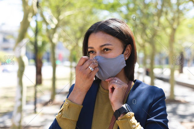 African American woman adjusting her face mask on the street. lifestyle living during coronavirus covid 19 pandemic.