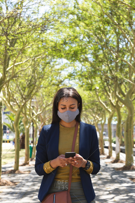 African American woman wearing face mask using smartphone on the street. lifestyle living during coronavirus covid 19 pandemic.