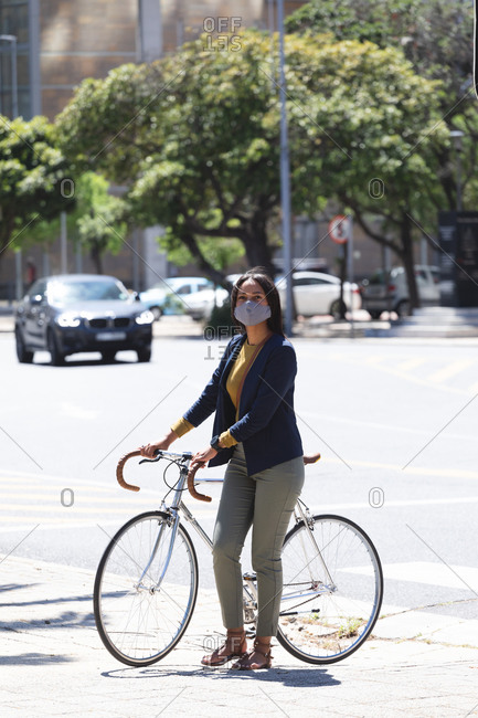 African American woman wearing face mask walking with bicycle on the street. lifestyle living during coronavirus covid 19 pandemic.