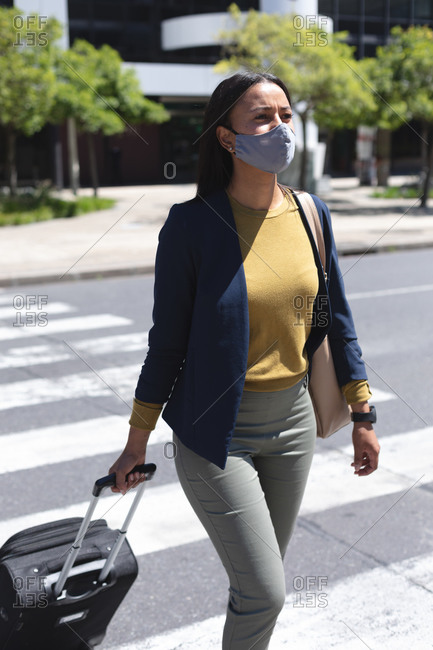 African American woman wearing face mask with trolley bag crossing the street. lifestyle living during coronavirus covid 19 pandemic.