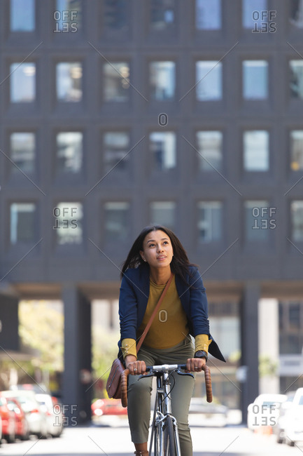 African American woman riding bicycle on the street. lifestyle living during coronavirus covid 19 pandemic.