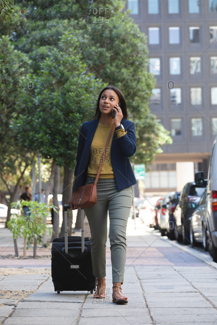 African American woman with trolley bag talking on smartphone while walking on the street. lifestyle living during coronavirus covid 19 pandemic.