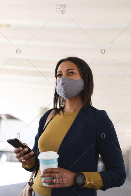 African American woman wearing face mask holding coffee cup and smartphone on the street. lifestyle living during coronavirus covid 19 pandemic.