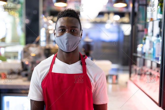 Portrait of African American male barista wearing face mask looking at the camera. health and hygiene in business during coronavirus covid 19 pandemic.