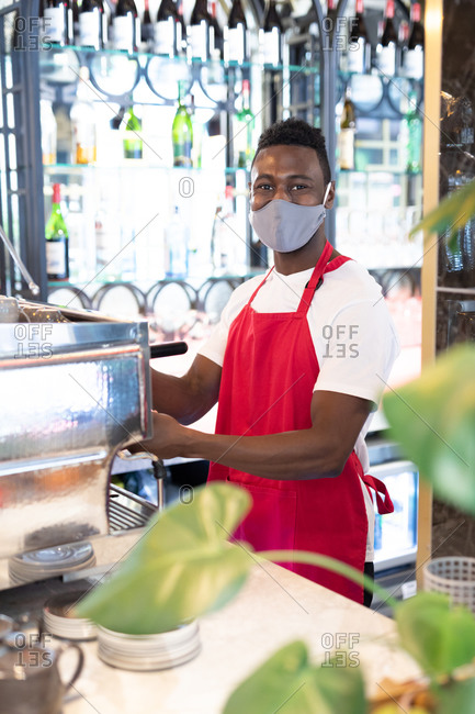 Portrait of African American male barista wearing face mask using coffee machine looking at camera. health and hygiene in business during coronavirus covid 19 pandemic.