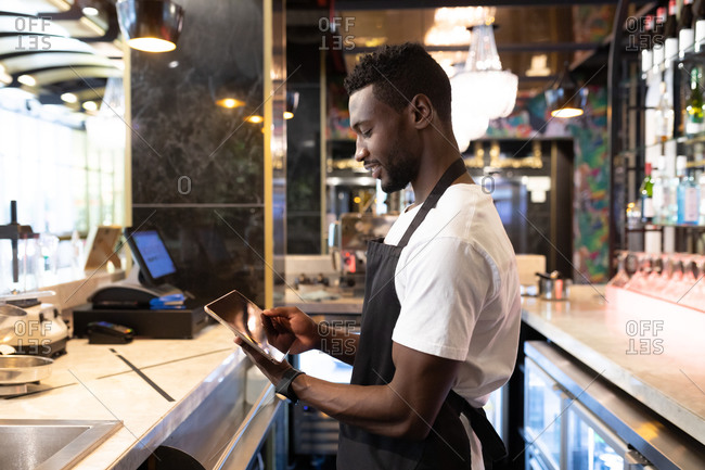 African American male barista standing behind a bar using a digital tablet and smiling. independent small business owner.