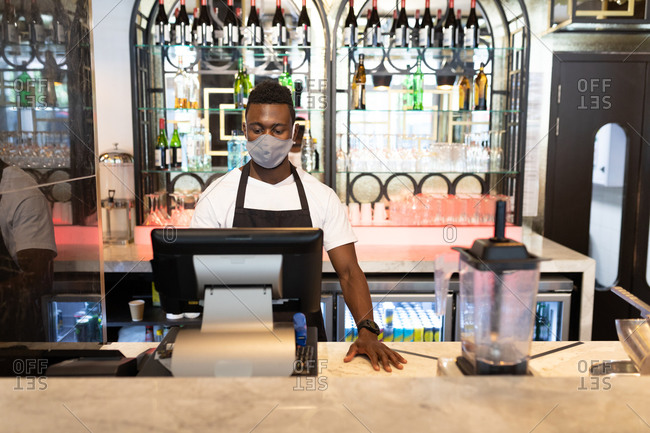 African American male barista wearing face mask using cash register. health and hygiene in business during coronavirus covid 19 pandemic.