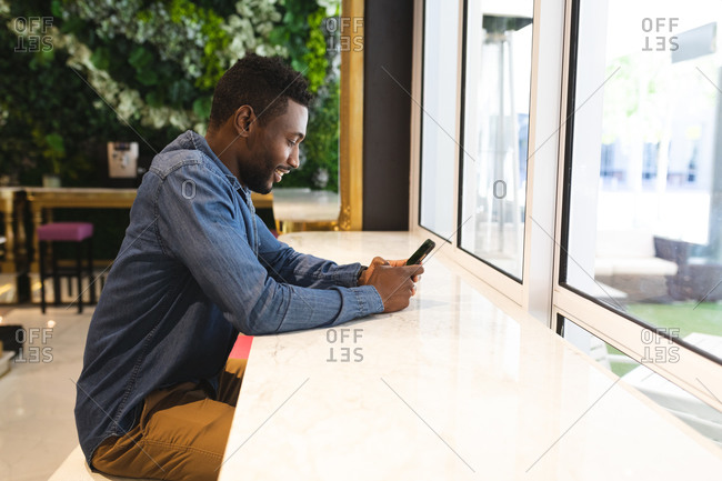 African American man sitting in a cafe using a smartphone and smiling. businessman on the go out in the city.