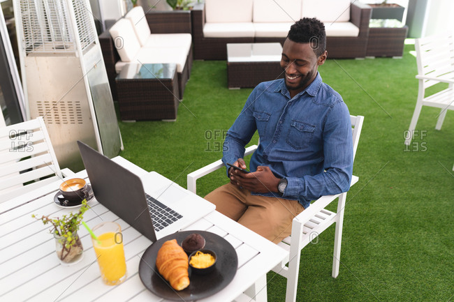African American man sitting in a cafe using smartphone and laptop eating breakfast. businessman on the go out in the city.