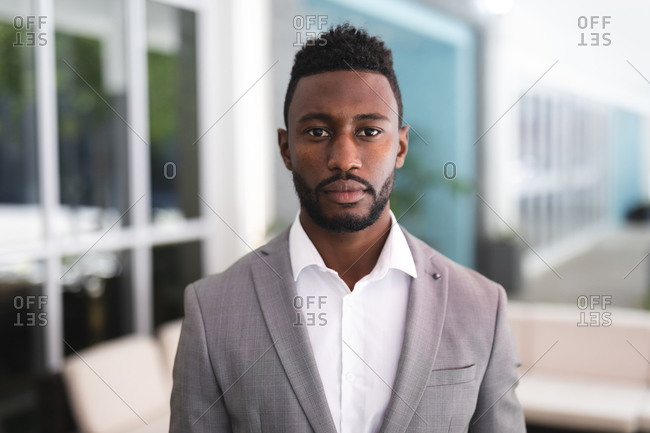 Portrait of African American male businessman standing in a cafe looking at camera. businessman on the go out in the city.