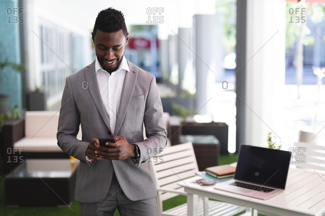 African American male businessman standing in a cafe and using smartphone. businessman on the go out in the city.