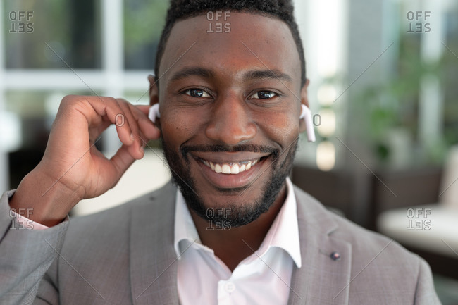 Portrait of African American male businessman standing in a cafe looking at camera. listening to music with earphones in. businessman on the go out in the city.