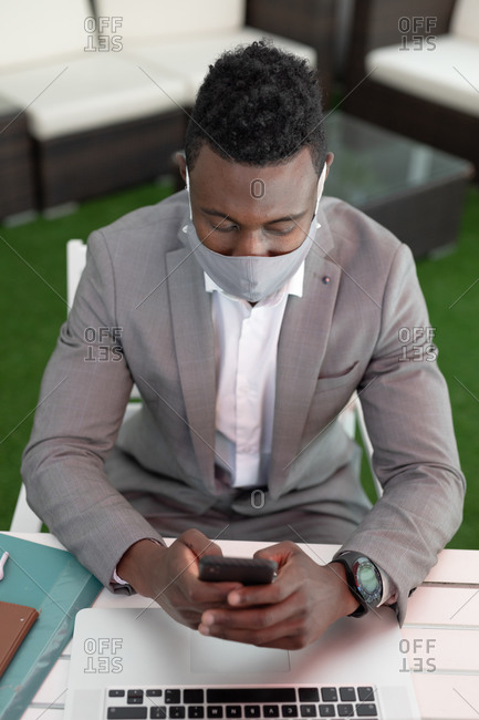 African American male businessman sitting in a cafe wearing face mask using smartphone and laptop. businessman on the go out in the city.
