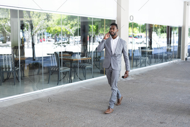 African American male businessman walking wearing face mask talking on smartphone. businessman on the go out in the city.
