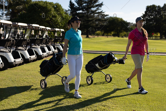 Two caucasian women walking across golf course pulling golf bags on wheels. sport leisure hobbies golf healthy outdoor lifestyle.