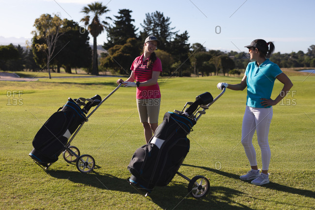 Two caucasian women on golf course holding golf bags and talking. sport leisure hobbies golf healthy outdoor lifestyle.