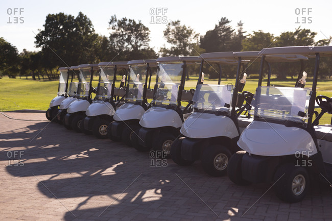 A row of golf buggies parked neatly at the edge of a golf course. sport leisure hobbies golf healthy outdoor lifestyle.