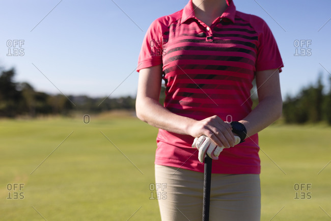 Midsection of caucasian woman standing on golf course holding golf club. sport leisure hobbies golf healthy outdoor lifestyle.