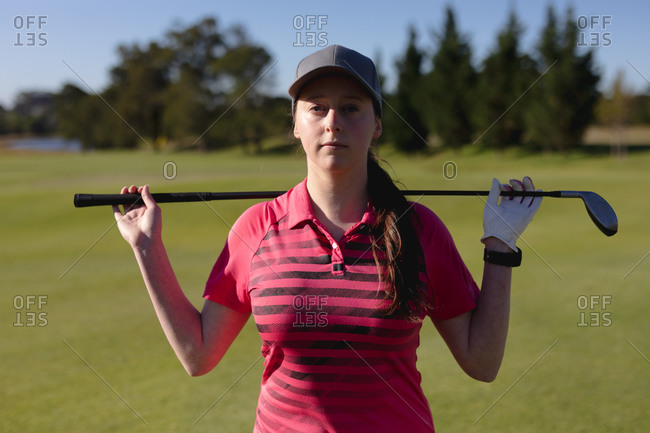 Portrait of caucasian woman on golf course holding golf club across shoulders. sport leisure hobbies golf healthy outdoor lifestyle.