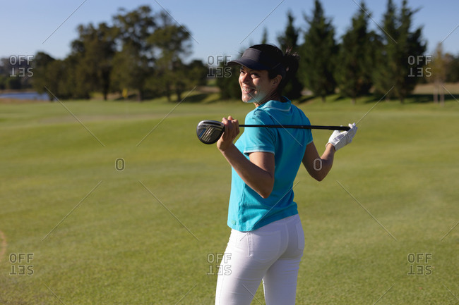 Caucasian woman on golf course holding golf club across shoulders smiling to camera. sport leisure hobbies golf healthy outdoor lifestyle.