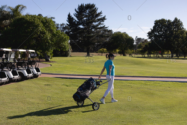 Caucasian woman walking across golf course pulling golf bag on wheels. sport leisure hobbies golf healthy outdoor lifestyle.