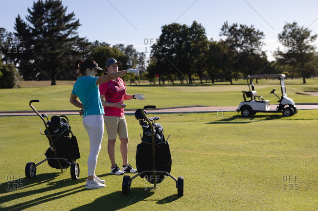 Two caucasian women with golf bags standing on golf course talking. sport leisure hobbies golf healthy outdoor lifestyle.