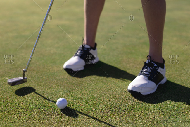 Low section of caucasian woman putting ball with club on golf course. sport leisure hobbies golf healthy outdoor lifestyle.