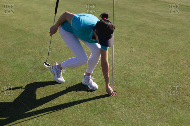 Caucasian woman playing golf taking ball from hole on golf course. sport leisure hobbies golf healthy outdoor lifestyle.