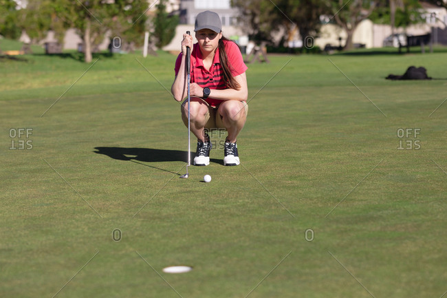 Caucasian woman playing golf squatting down before taking her shot at hole. sport leisure hobbies golf healthy outdoor lifestyle.